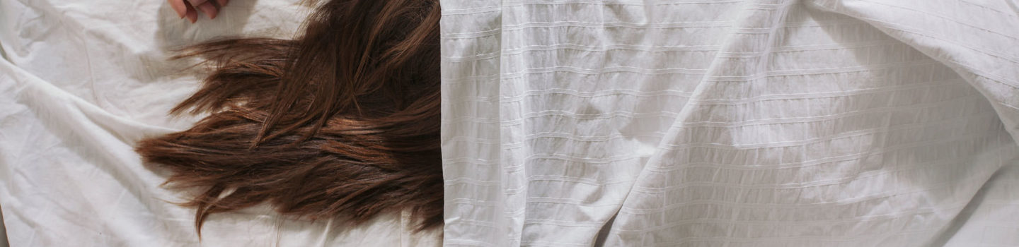 Girl's hair peeking out under sheets