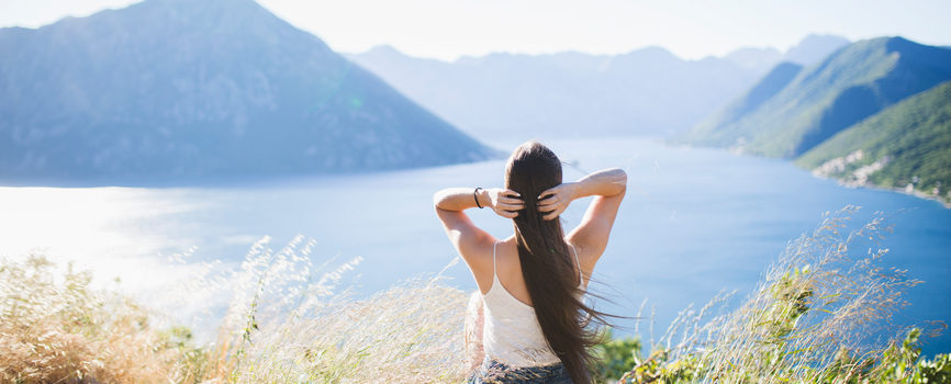 Woman becoming morning person by sitting on mountain overlooking ocean